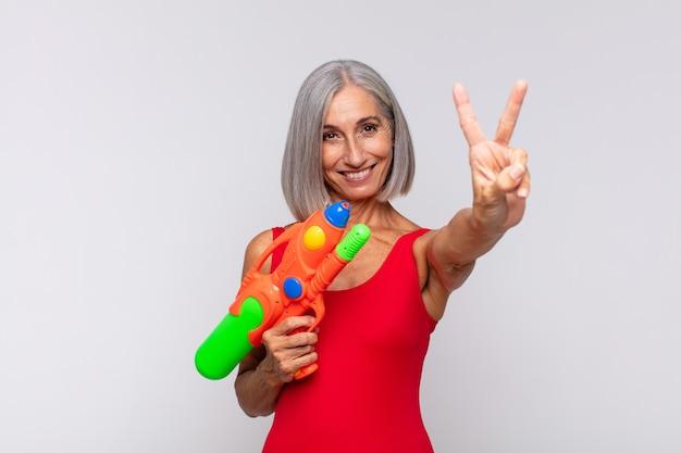 Donna di mezza età che sorride e sembra felice, spensierata e positiva, gesticola la vittoria o la pace con una mano con una pistola ad acqua