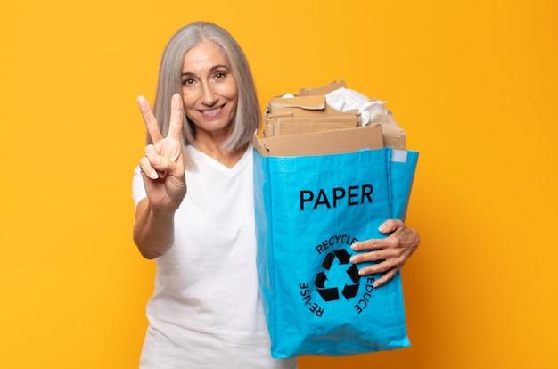 Donna di mezza età che sorride e sembra felice, spensierata e positiva, gesticolando vittoria o pace con una mano
