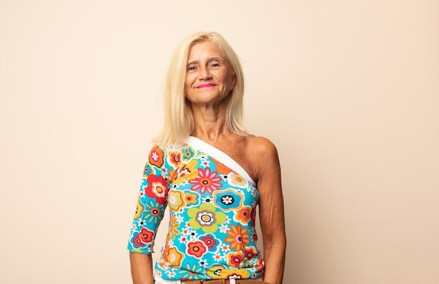 Donna di mezza età che sorride positivamente e con sicurezza, sembra soddisfatta, amichevole e felice