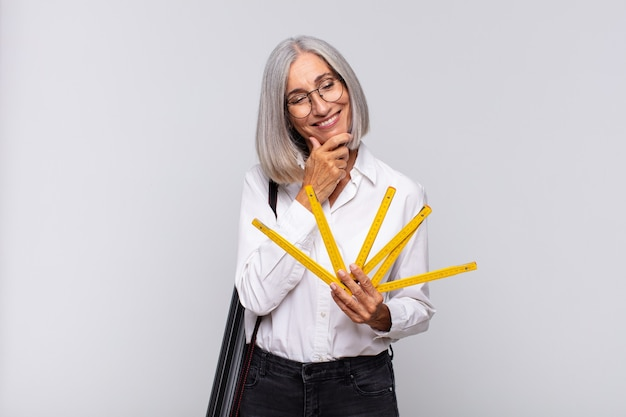 Donna di mezza età che sorride con un'espressione felice e sicura con la mano sul mento, chiedendosi e guardando di lato. concetto di architetto