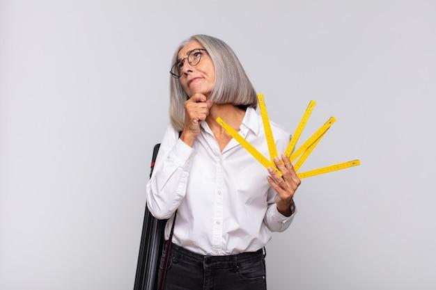 Donna di mezza età che pensa, si sente dubbiosa e confusa, con diverse opzioni, chiedendosi quale decisione prendere. concetto di architetto