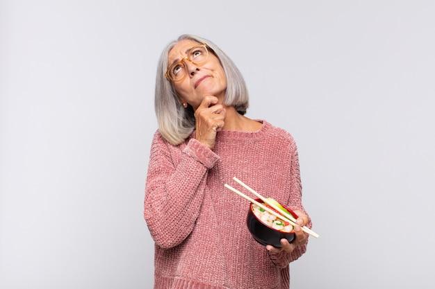 Donna di mezza età che pensa, si sente dubbiosa e confusa, con diverse opzioni, chiedendosi quale decisione prendere per il concetto di cibo asiatico