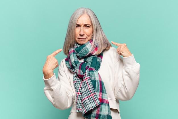 Donna di mezza età con un cattivo atteggiamento che sembra orgogliosa e aggressiva, che punta verso l'alto o che fa un segno divertente con le mani