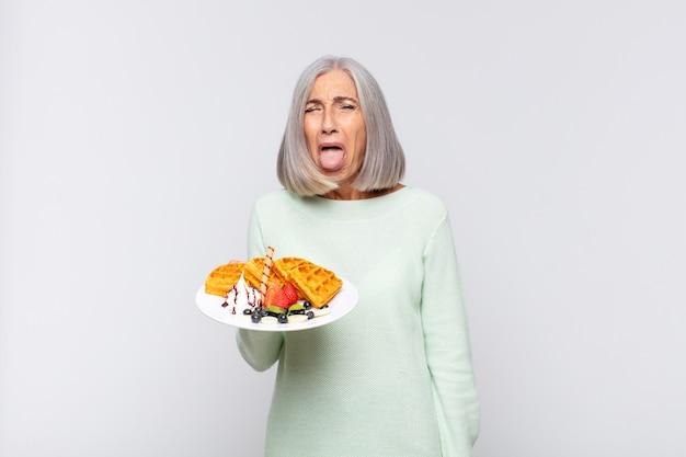 Donna di mezza età con atteggiamento allegro, spensierato, ribelle, scherzando e tirando fuori la lingua, divertendosi. concetto di colazione