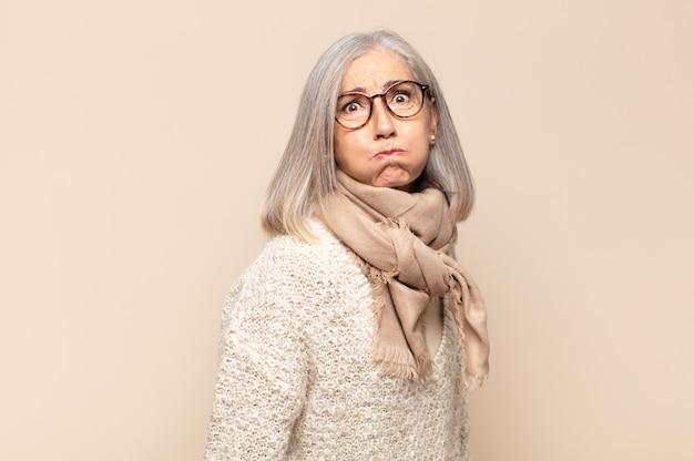 Donna di mezza età con un'espressione sciocca, pazza, sorpresa, guance gonfie, sentirsi imbottita, grassa e piena di cibo