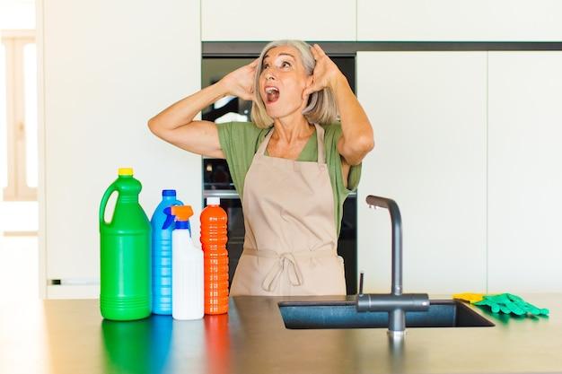 Donna di mezza età con la bocca aperta, inorridita e scioccata a causa di un terribile errore, alzando le mani alla testa