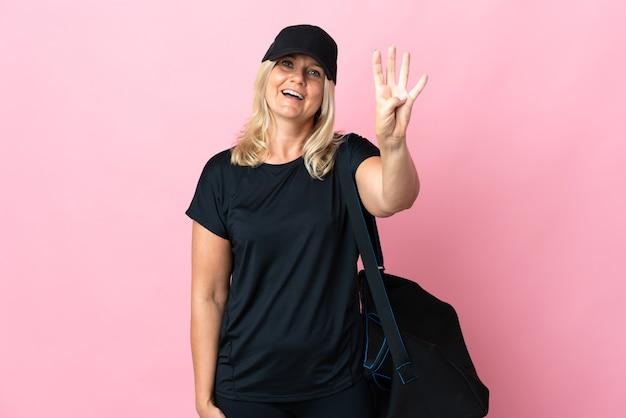 Donna di mezza età con borsa sportiva isolata sul rosa felice e contando quattro con le dita