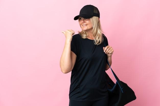 Donna di mezza età con borsa sportiva isolata sul colore rosa che punta di lato per presentare un prodotto
