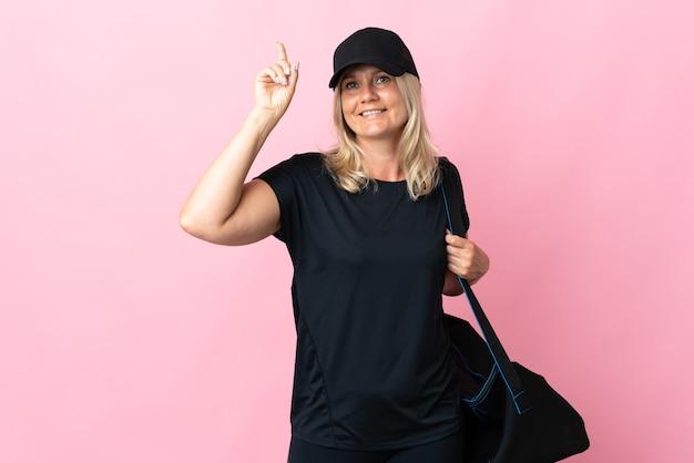 Donna di mezza età con borsa sportiva isolata sul rosa rivolto verso l'alto una grande idea