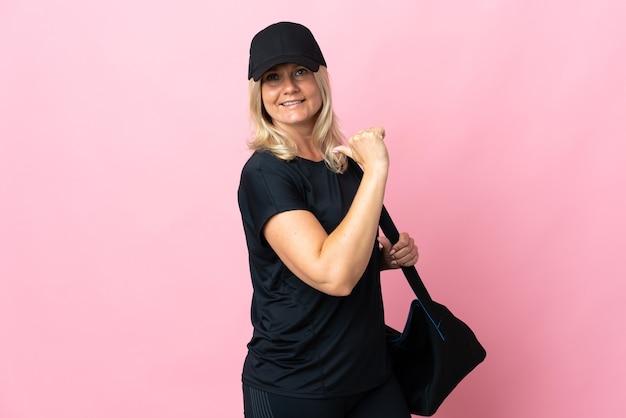Donna di mezza età con borsa sportiva isolata su rosa orgogliosa e soddisfatta