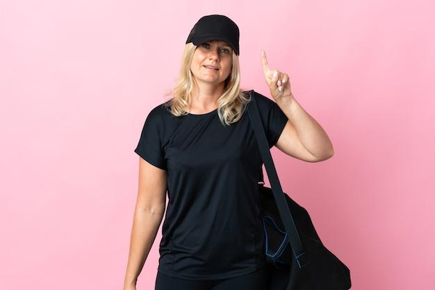 Donna di mezza età con borsa sportiva isolata sulla mostra rosa e alzando un dito in segno del meglio