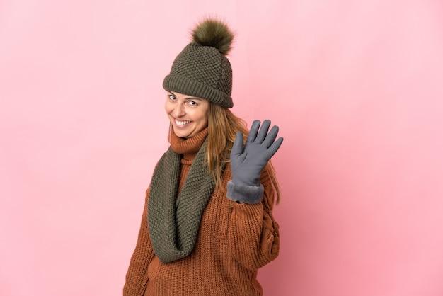 Donna di mezza età con cappello invernale isolato sulla parete rosa che saluta con la mano con l'espressione felice