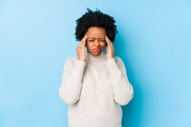 La donna afroamericana di mezza età contro uno sfondo blu isolato toccando le tempie e avendo mal di testa.