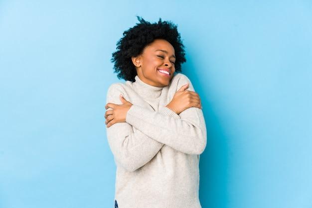 Donna afroamericana di mezza età contro un abbraccio isolato blu, sorridente spensierata e felice.