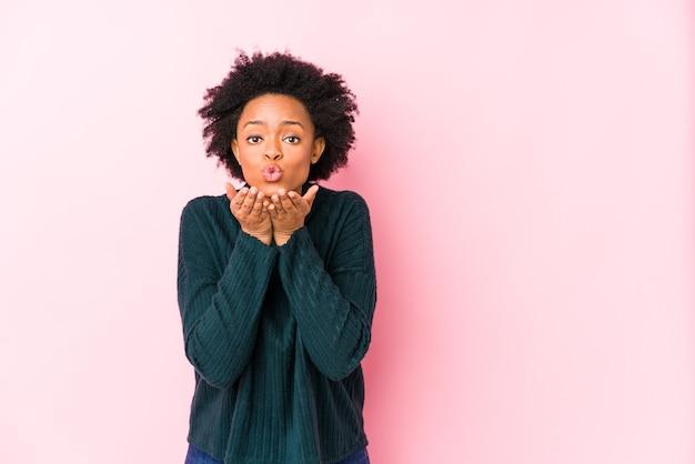 La donna afroamericana di mezza età contro uno sfondo rosa ha isolato le labbra pieghevoli e le palme della holding per inviare un bacio d'aria.
