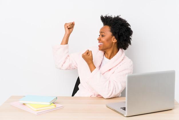 Donna afroamericana di mezza età che lavora a casa isolata alzando il pugno dopo una vittoria, concetto di vincitore.