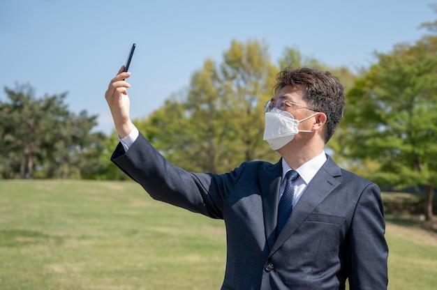 Uomo d'affari asiatico di mezza età che indossa una maschera e utilizza uno smartphone sul prato.