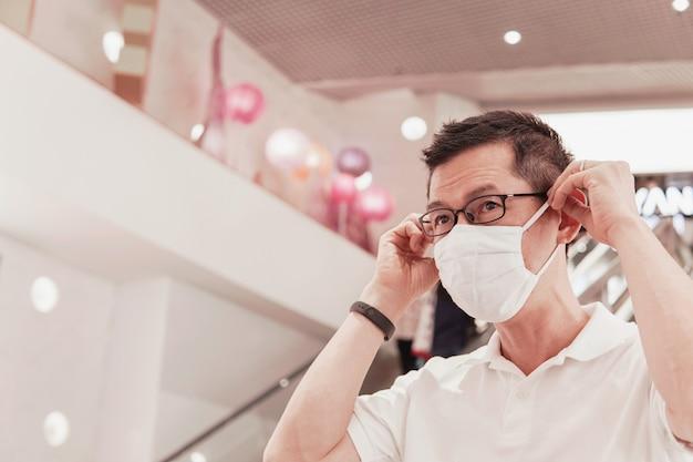 Vetri d'uso dell'uomo asiatico invecchiato mezzo e maschera di protezione medica nel centro commerciale, scoppio di coronavirus di wuhan, inquinamento atmosferico e concetto di salute