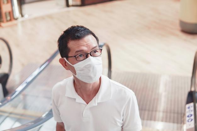 Vetri d'uso dell'uomo asiatico invecchiato centrale e maschera di protezione medica, scoppio del coronavirus di wuhan, inquinamento atmosferico e concetto di salute