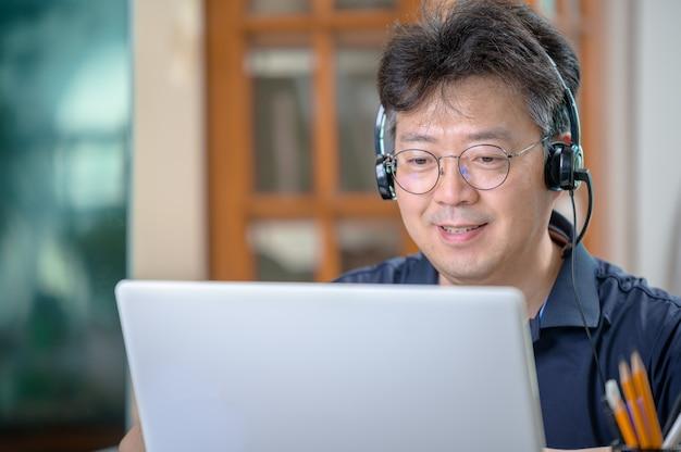 Uomo asiatico di mezza età che lavora a casa. concetto di telelavoro.