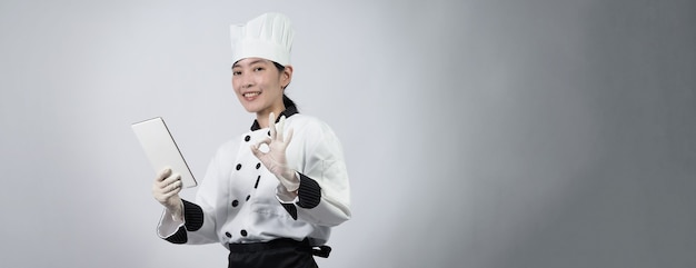 Di mezza età di chef donna asiatica che tiene smartphone o tablet digitale e ha ricevuto l'ordine dal negozio online o dall'applicazione commerciale.
