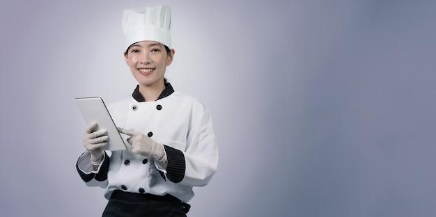 Cuoco di mezza età di una donna asiatica che tiene in mano uno smartphone o un tablet digitale e ha ricevuto l'ordine da online