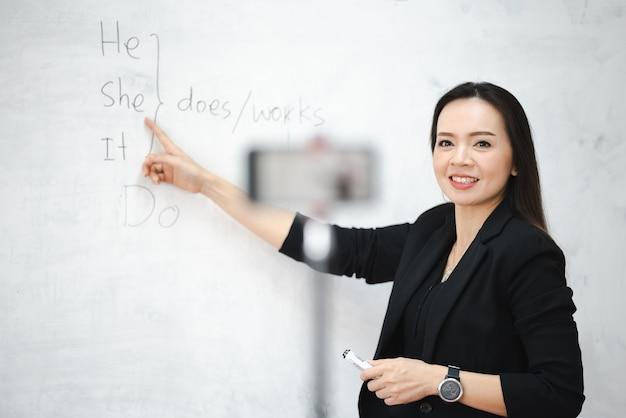 Un'insegnante asiatica di mezza età vive online con lo smartphone all'università