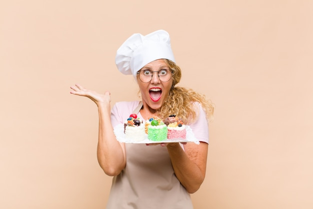 Donna invecchiata centrale del panettiere che cucina le torte