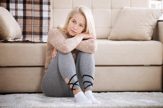 Donna a piedi nudi di mezza età seduta sul pavimento che abbraccia le ginocchia, vicino al divano di casa, a testa bassa, annoiata, turbata dalla violenza domestica.