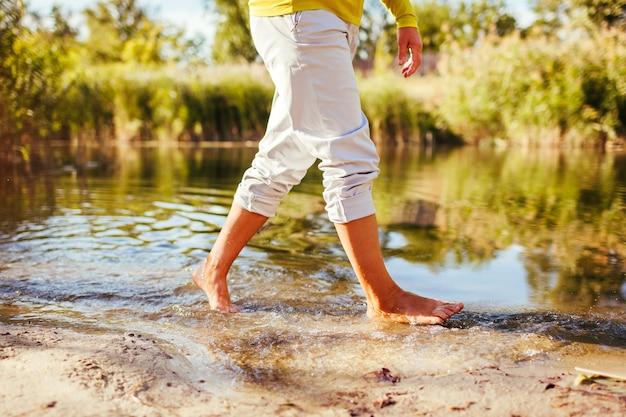 Donna scalza di mezza età che cammina sulla riva del fiume il giorno d'autunno. signora anziana che si diverte nella foresta per godersi la natura. primo piano delle gambe