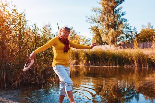 Donna scalza di mezza età che cammina sulla riva del fiume il giorno d'autunno. signora anziana che si diverte nella foresta godendosi la natura