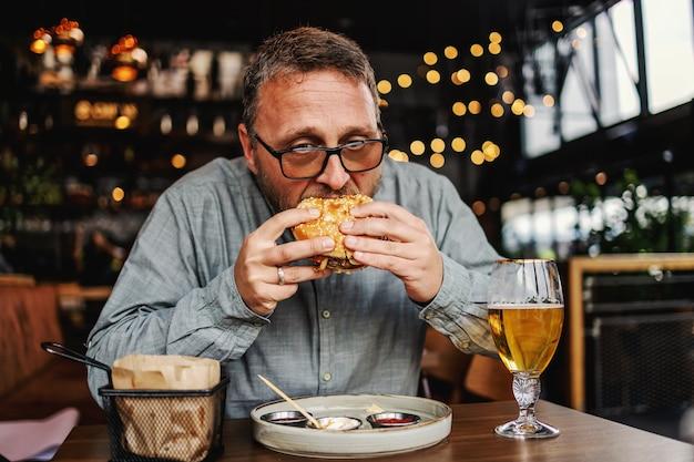 Uomo barbuto affamato di mezza età seduto al ristorante e mangiare delizioso hamburger.