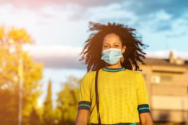 Donna nera di mezza età con capelli afro, che indossa una maschera in strada. concetto di pandemia di coronavirus.