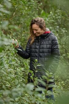 Donna sorridente bionda di mezza età che cammina nella boscaglia in inverno, tra le foglie degli alberi. indossa una giacca calda.