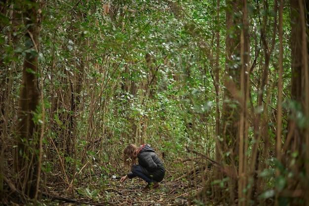 Donna bionda di mezza età nella foresta per godersi la natura in inverno. accovacciato guardando le piante. tra gli alberi.