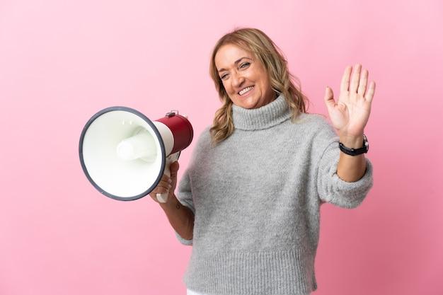 Donna bionda di mezza età sopra fondo rosa isolato che tiene un megafono e che saluta con la mano con l'espressione felice