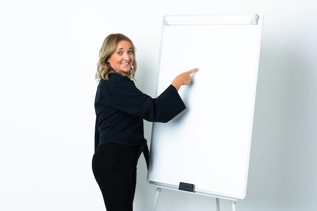 Donna bionda di mezza età sopra bianco isolato che dà una presentazione sulla lavagna bianca e scrivendo in esso