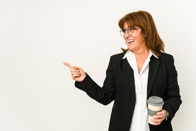 Donna di mezza età di affari che tiene un caffè da asporto isolato sorridendo e indicando da parte, mostrando qualcosa in uno spazio vuoto.