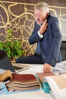 Uomo d'affari di mezza età seduto alla scrivania con piani di costruzione e cataloghi di tessuto da tappezzeria quando si parla al telefono con il cliente