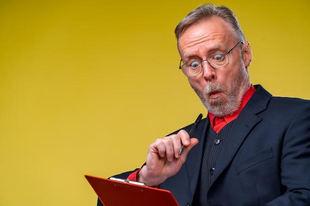 Uomo d'affari di mezza età in piedi e in possesso di una cartella di file. formato orizzontale isolato su sfondo giallo.