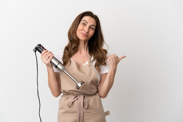Donna caucasica di mezza età che utilizza frullatore a immersione isolato su sfondo bianco rivolto verso il lato per presentare un prodotto