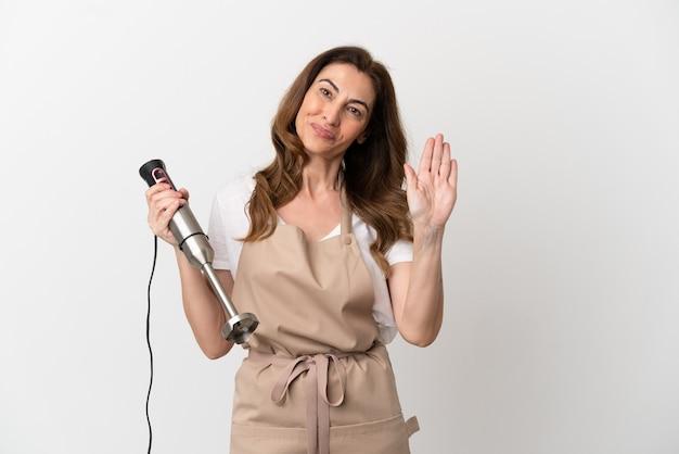 Donna caucasica di mezza età che utilizza frullatore a immersione isolato su sfondo bianco salutando con la mano con espressione felice