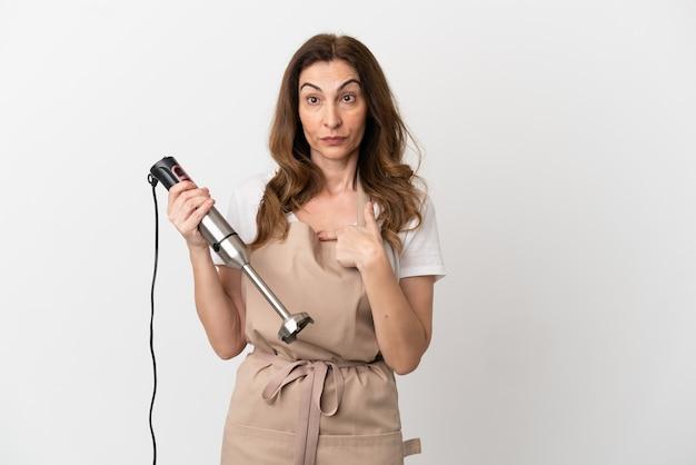 Donna caucasica di mezza età che utilizza frullatore a immersione isolato su sfondo bianco con espressione facciale a sorpresa