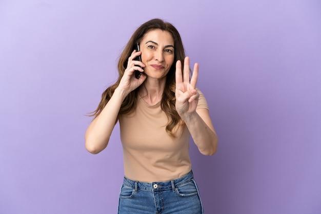 Donna caucasica di mezza età che utilizza il telefono cellulare isolato su sfondo viola felice e contando tre con le dita