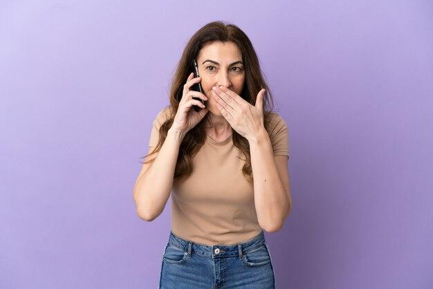 Donna caucasica di mezza età che utilizza il telefono cellulare isolato su sfondo viola felice e sorridente che copre la bocca con la mano