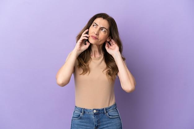 Donna caucasica di mezza età che utilizza il telefono cellulare isolato su sfondo viola avendo dubbi