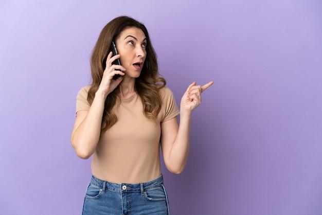 Donna caucasica di mezza età che utilizza il telefono cellulare isolato su sfondo viola con l'intenzione di realizzare la soluzione mentre si solleva un dito