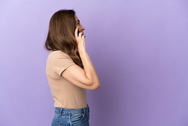 Donna caucasica di mezza età che utilizza il telefono cellulare isolato su sfondo viola che ride in posizione laterale