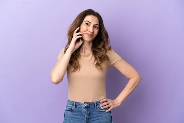 Donna caucasica di mezza età che utilizza il telefono cellulare isolato su sfondo viola in posa con le braccia all'anca e sorridente