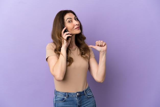 Donna caucasica di mezza età che utilizza il telefono cellulare isolato su sfondo viola orgoglioso e soddisfatto di sé
